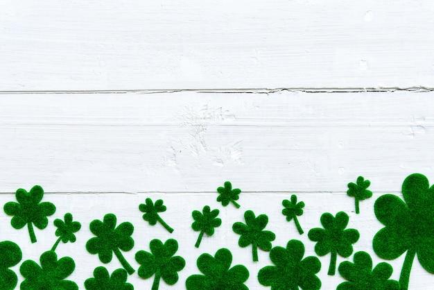 Um monte de folhas de trevo de papel verde sobre fundo branco de madeira
