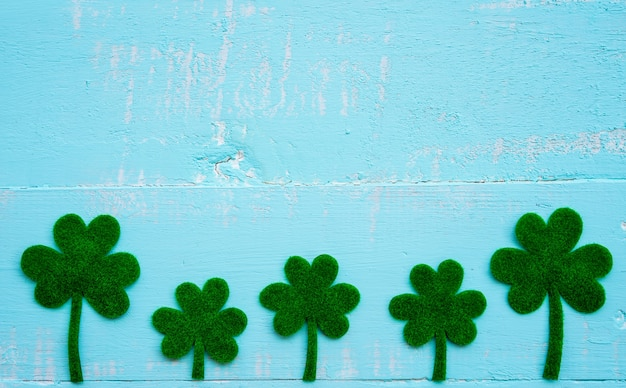 Um monte de folhas de trevo de papel verde sobre fundo branco e azul mesa de madeira