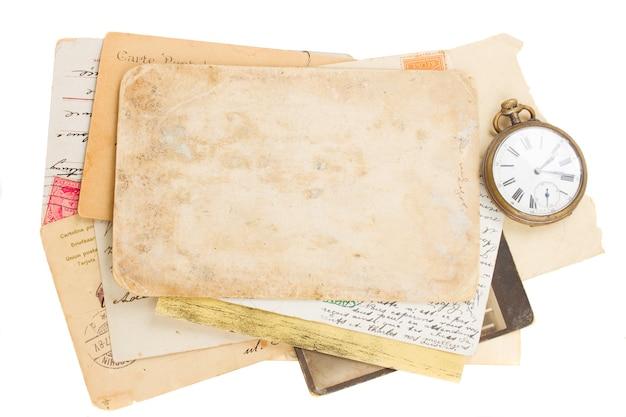 Um monte de fotos e papéis antigos com um relógio antigo e uma chave isolada no fundo branco