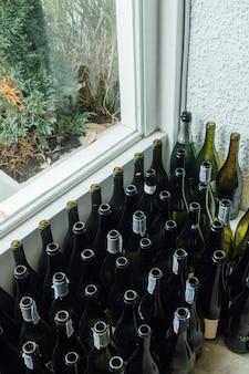 Um monte de garrafas vazias de vinho em uma sala perto da janela