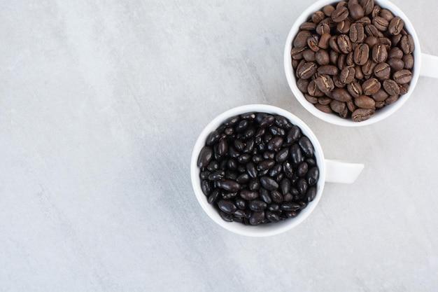 Um monte de grãos de café e gotas de chocolate em xícaras