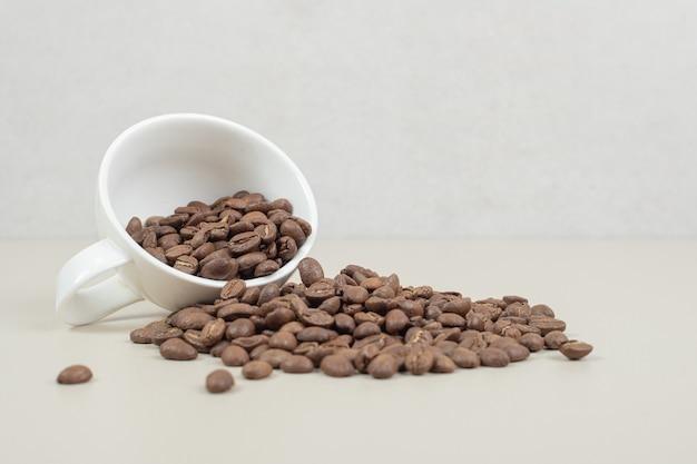 Um monte de grãos de café em uma caneca branca