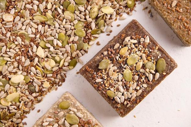 Um monte de halva diferente em um fundo branco ao lado dos ingredientes, sementes em um fundo branco. vista de cima. doces saudáveis