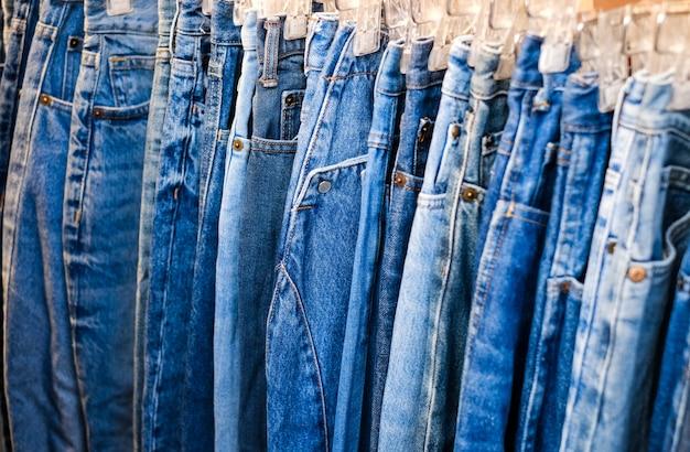 Um monte de jeans está pendurado em um cabide na loja. uma linha de calças jeans em um cabide na loja. venda de jeans na loja no balcão. textura de jeans