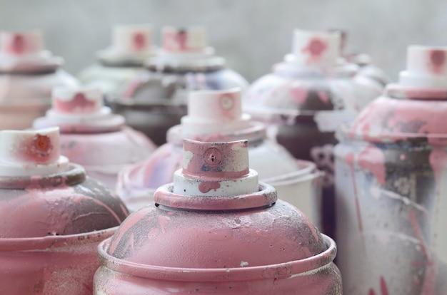 Um monte de latas de aerossol sujo e usado de tinta rosa brilhante.