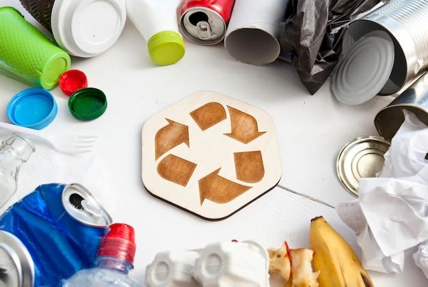 Um monte de lixo diferente na mesa e ícone de reciclagem entre eles