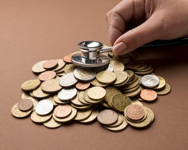 Um monte de moedas com uma pessoa usando um estetoscópio
