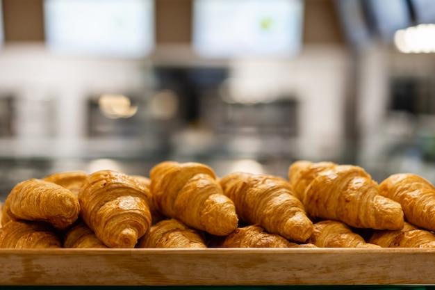 Um monte de pão fresco pronto em uma padaria com loja de padaria turva na loja de atacado com máquina de cozimento,