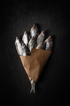 Um monte de peixe seco em um fundo preto com papel ofício