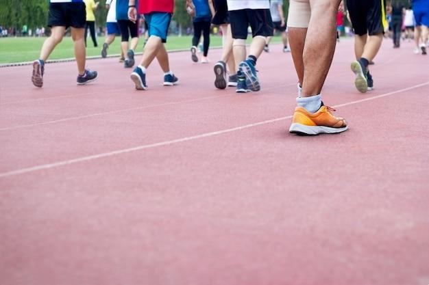 Um monte de pessoas andando excercise em fundo de pista de corrida