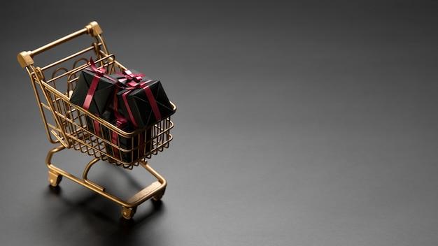 Um monte de presentes pretos de sexta-feira em um carrinho de compras dourado com espaço de cópia