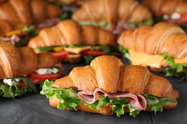 Um monte de saborosos sanduíches de croissant na mesa cinza