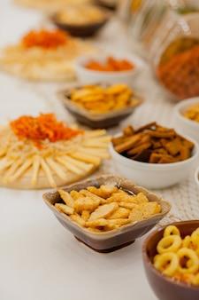 Um monte de salgadinhos em uma mesa, muitos queijos e bolachas em cima da mesa com salgadinhos