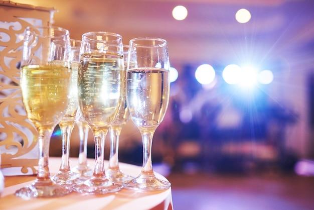 Um monte de taças de vinho em luz azul com um delicioso champanhe fresco ou vinho branco no bar.