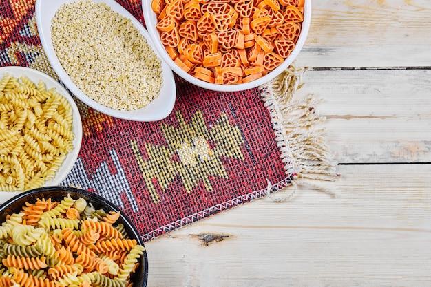 Um monte de tigelas de macarrão cru colorido na mesa de madeira com pano esculpido.