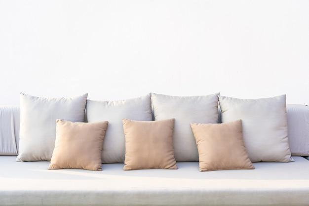 Um monte de travesseiro confortável no interior da decoração do sofá da sala
