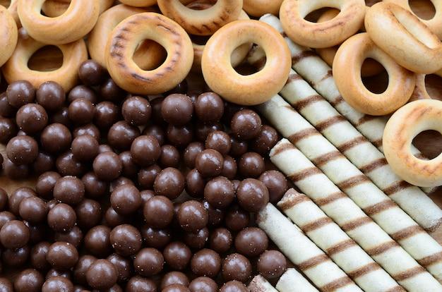 Um monte de túbulos doces crocantes, bolas de chocolate derretendo e bagels amarelos