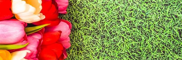 Um monte de tulipas coloridas frescas brilhantes sobre um fundo de grama.
