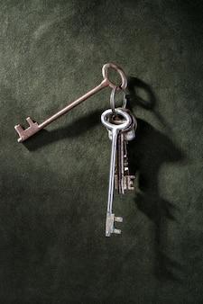 Um monte de velhas chaves de metal em uma superfície verde