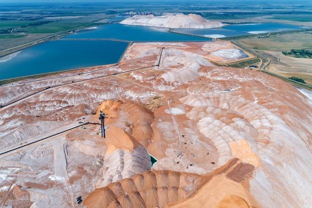 Um monte enorme de sal de potássio. armazenagem de rochas com a ajuda de um espalhador