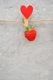 Um morango maduro vermelho pendurado no prendedor de madeira com corações no fio da corda, localizado na borda superior em pedra cinza