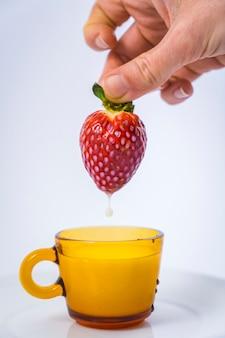Um morango mergulhando em um copo de leite pela mão de uma mulher