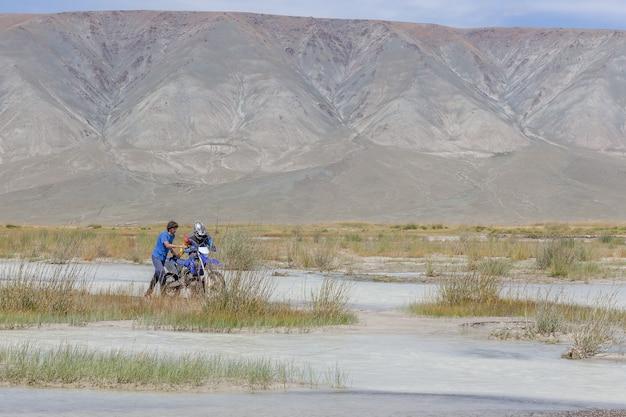 Um motociclista conduz uma motocicleta por um rio da montanha branca, seu amigo o ajuda. mongólia, altai.