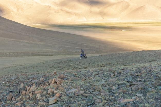 Um motociclista experimenta sua motocicleta nas colinas da mongólia