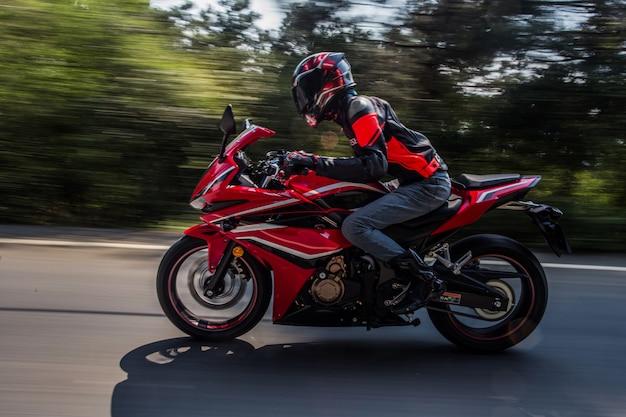 Um motociclista que anda de bicicleta na estrada.