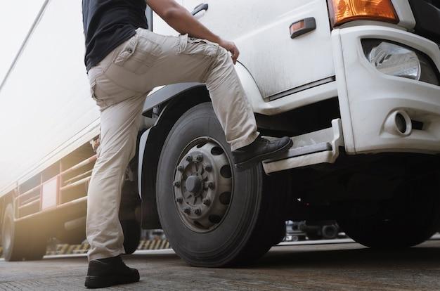 Um motorista de caminhão parado com um caminhão de contêineres de carga.