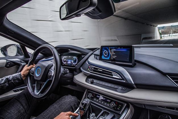 Um motorista dirigindo um carro, vista interior.