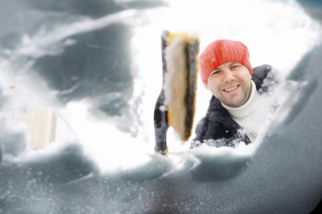 Um motorista do sexo masculino está parado na frente de um carro. o proprietário limpa o carro da neve no inverno. carro depois de uma nevasca.