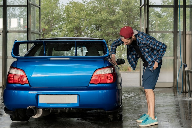 Um motorista do sexo masculino limpando o carro dentro da caixa da estação de autolavagem