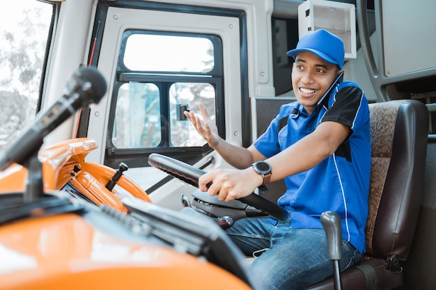 Um motorista do sexo masculino uniformizado com gesto de mão ao ligar enquanto dirige o ônibus
