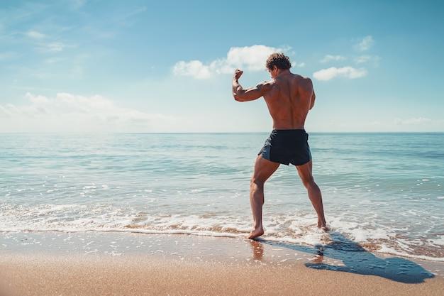 Um muay thai ou kickboxer treinando com boxe de sombra ao ar livre na praia