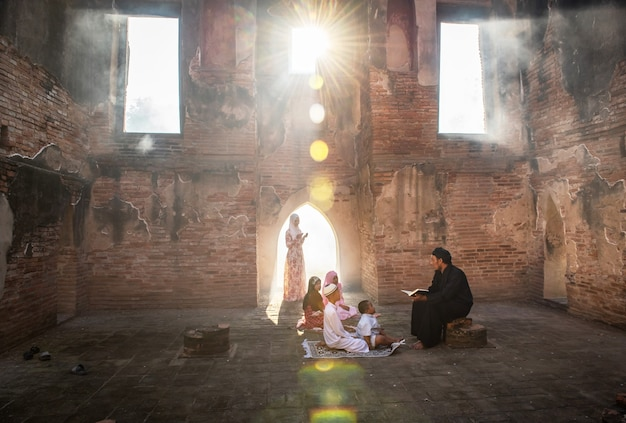 Um muçulmano asiático ensinou seu filho e sua filha a ler orações a deus em uma mesquita com a luz do sol brilhando através das janelas e portas.