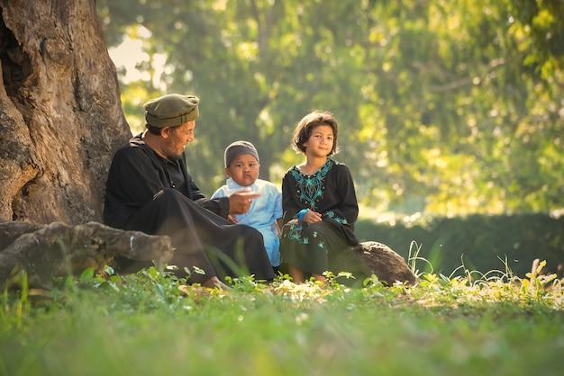 Um muçulmano asiático que ensina sua filha pequena, lê orações sob as árvores no gramado de casa, com o sol da manhã brilhando lindamente.