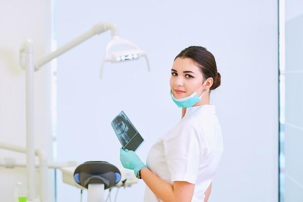 Um, mulher dentista, com, raio x, local trabalho, em, dental, escritório