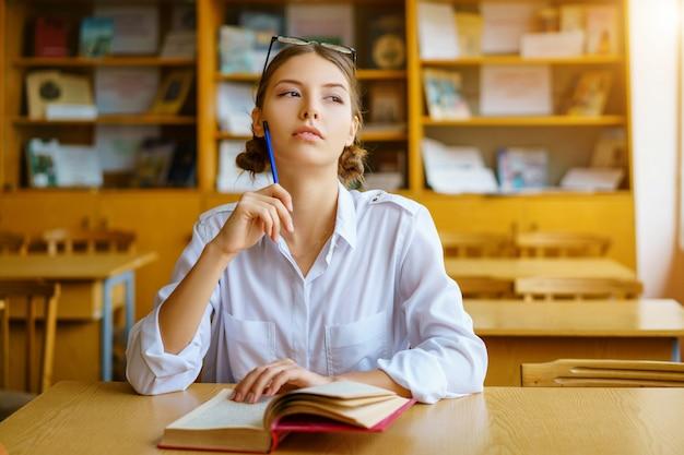 Um, mulher jovem, sentando, em, um, escrivaninha, em, um, camisa branca