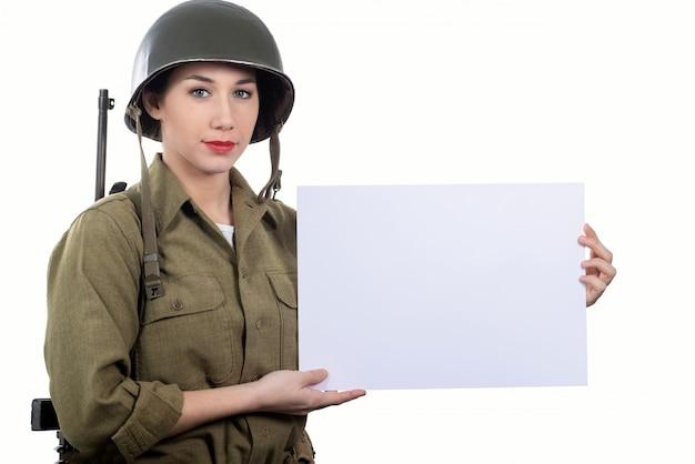 Um, mulher jovem, vestido, em, americano, ww2, uniforme militar, mostrando, vazio, em branco, signboard