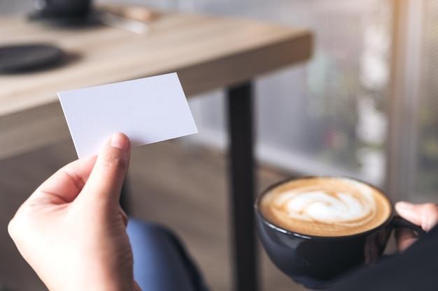 Um, mulher segura, um, vazio, cartão negócio, enquanto, bebendo, xícara café