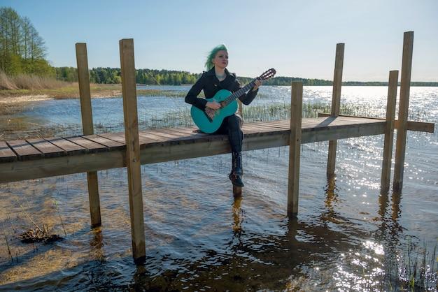 Um músico com cabelos azuis e um violão azul senta-se na passarela do lago e toca música.
