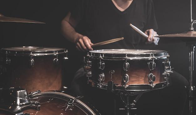 Um músico com uma camiseta preta toca bateria com baquetas no palco.