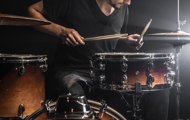 Um músico toca bateria com baquetas no palco com iluminação de palco.