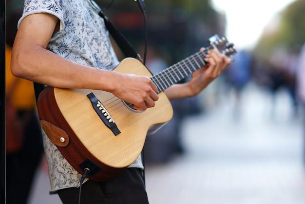 Um músico toca violão, detalhe das mãos