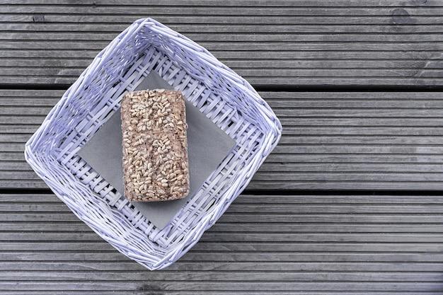 Um naco de pão encontra-se em uma cesta roxa em uma tabela de madeira.