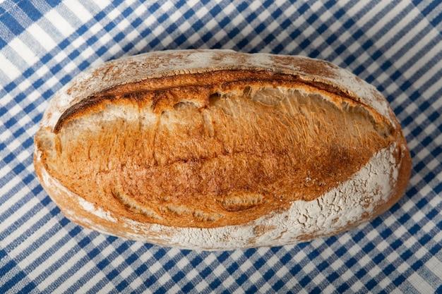 Um naco de pão fresco sobre uma mesa de madeira. vista superior com espaço de cópia.