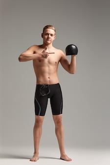 Um nadador, um jovem atleta em excelente forma física, mostra com a mão instando para começar os treinos, um banner publicitário, um fundo cinza, uma cópia do espaço.