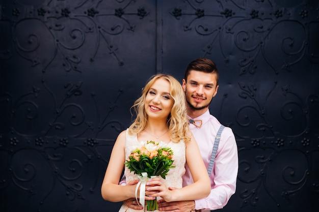 Um namorado abraça sua namorada que segurando um buquê de flores no fundo da porta preta
