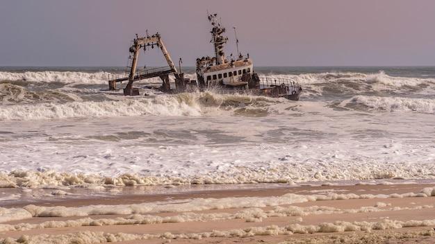 Um naufrágio encalhado na praia no oceano atlântico no parque nacional da costa do esqueleto na namíbia, áfrica.